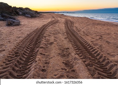 Tire tread marks on sand by sea