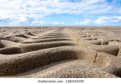 Tire tread in sand low angle to the ground with blue sky clouds horizon