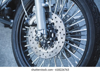 Tire, wheel, brakes, and related items on the front of a modern motorcycle.