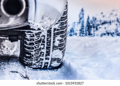 Tire in winter on snow road. Winter tires with car detail.
