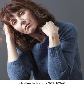 tired 50's woman holding her head and hair for depression, loss or fatigue due to menopause