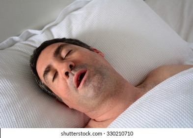 Tired adult man (age 30-40) snoring in bed. Male health care and medical concept. Real people. Copy space