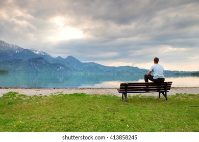 Tired adult man in blue shirt sit on old wooden bench at mountains lake coast. Vintage photo effect