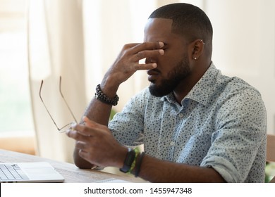 Tired african american businessman student holding glasses rubbing dry eyes feeling eye strain headache after computer work, overworked stressed black man having bad blurry weak sight vision problem