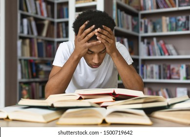 Tired african american guy holding head and looking at book, getting ready for exams, library interior