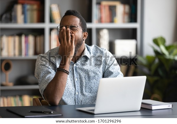 Tired african American male worker or student sit at desk sigh yawn feeling stressed or fatigue overwork in office, exhausted biracial man suffer from insomnia, need sleep or rest, exhaustion concept