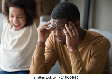 Tired african american single dad touch massage temples suffer from severe headache or dizziness, happy disobedient small daughter have fun playing scream making noise at background. Fatigue concept