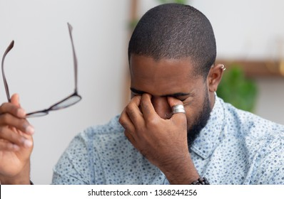 Tired african businessman taking off glasses rubbing dry irritated eyes feeling fatigue headache pain eyestrain, black overworked man massage nose bridge suffer from bad weak vision problem tension