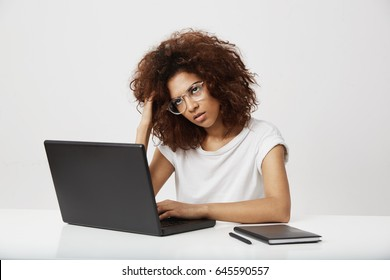 Tired african businesswoman thinking working at laptop over white background.
