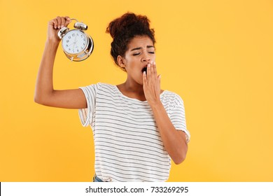 Tired african woman yawns and holding alarm clock over yellow background