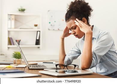 Tired african-american business woman with headache at office, feeling sick at work, copy space