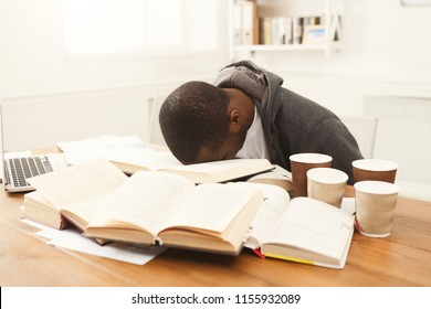 Tired african-american student studying at working table. Exhausted male student preparing for exams, drinking lots of coffee and falling asleep. Education and overworking concept