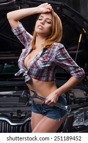Tired after hard working day. Beautiful young woman with beautiful cleavage holding big wrench and keeping eyes closed while standing near the car in auto repair shop