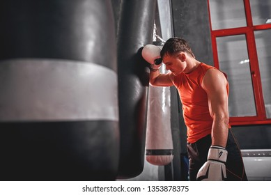 Tired after workout. Tired young athlete in sports clothing looking away after hard training on heavy punch bag in boxing gym