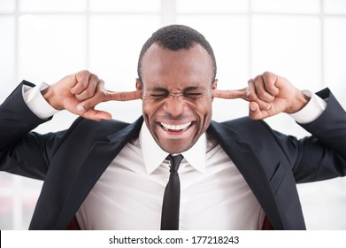Tired of it all. Young African man in formalwear closing his ears with fingers and keeping eyes closed while sitting at his working place