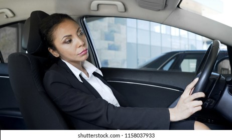Tired annoyed business woman stuck in traffic jam, late for important meeting