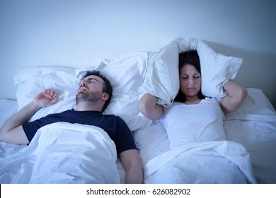 Tired and annoyed woman of her boyfriend snoring in the bed