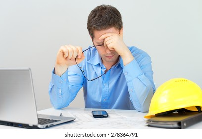 Tired architect working at his workplace.