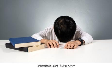Tired asian boy falling asleep while doing his homework