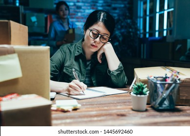tired Asian business lady in glasses look at customer address on pastal package writing down on notebook with hand in chin. girl colleague with parcel boxes walk in background at dark office in night