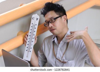 Tired Asian business man with thermometer sitting and sweating after work. Summer heat day concept.