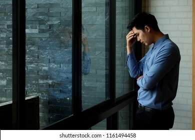 Tired Asian businessman standing in side of the big window in office