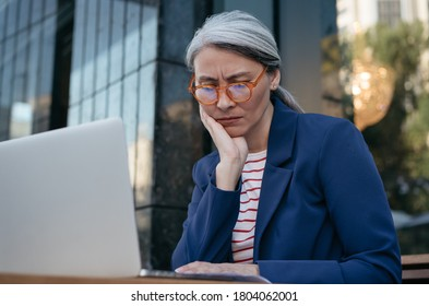 Tired asian businesswoman working project, using laptop, searching information, brainstorming. Portrait of frustrated mature woman sitting at workplace