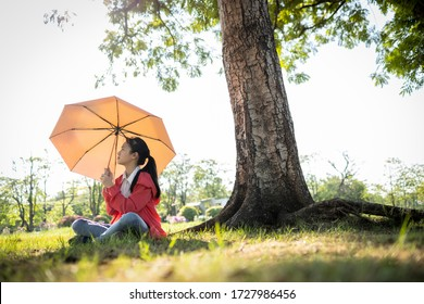 Tired asian child girl is holding umbrella uv to covering face skin,protection from sunlight ray,high temperature on sunny day,prevent heatstroke,sunburn very hot in summer weather problem,feel faint