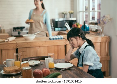 Tired asian chinese little girl in uniform before school fell asleep in early morning waiting for breakfast not enough sleep. elegant wife mom in apron busy prepare handmade delicious healthy meal