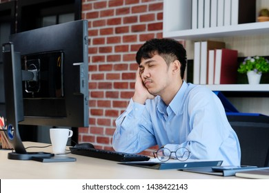 Tired asian man sleeping at office desk. Young businessman with eyeglasses overworked and fell asleep, Creative casual man sleeping at his working place