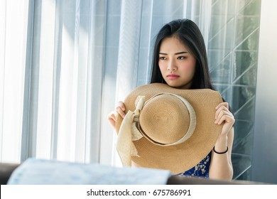 Tired Asian traveler waiting for delayed transportation in hotel. Bored frustrated young woman while traveling on summer vacation.