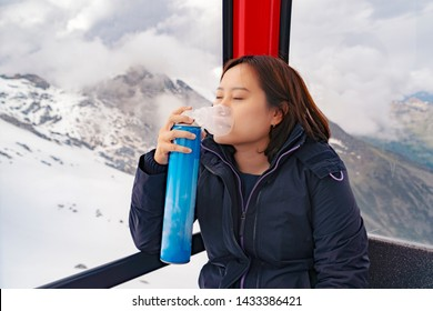 Tired Asian woman getting extra oxygen using oxygen can in a cable car on the high mountain lake where there is thin air or less oxygen, use for preventing Altitude mountain sickness (AMS) symptom
