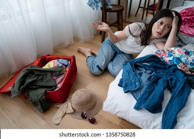 tired asian woman sit on floor near bed with clothes while packing before trip travel concept. angry girl frowning with hand gesturing dislike new year holidays back to home town feeling annoying.