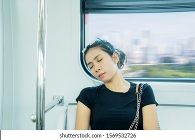 Tired Asian woman sleeping while riding to home after work in train