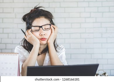 tired Asian woman sleepy taking a nap at work sitting at office desk
