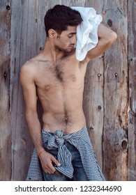 Tired athlete after workout session resting outdoors. Exhausted young handsome, muscular young worker shirtless outdoor. Handsome man after workout or nad work outdoors agaist wooden fence.
