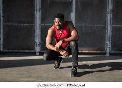 Tired athlete resting during urban running outdoor workout.