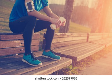 Tired athlete resting on the bench in park with bottle of water (intentional sun glare and vintage color)