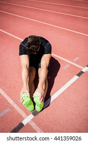 Tired athlete sitting on the running track on a sunny day