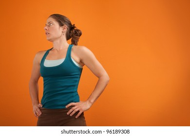 Tired athletic Caucasian woman with hands one hips