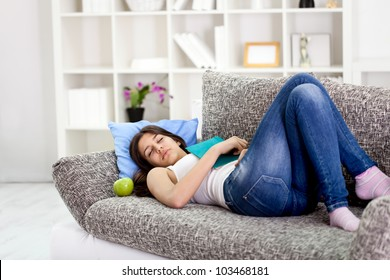 tired beautiful teenage girl sleeping on sofa at home