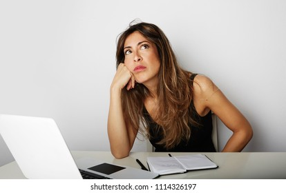 Tired beautiful young woman dreaming over empty white background. Laptop and note pad on the table. Horizontal