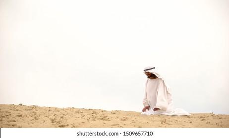 Tired Bedouin kneeling in desert, exhausted and lost, overcoming difficulties