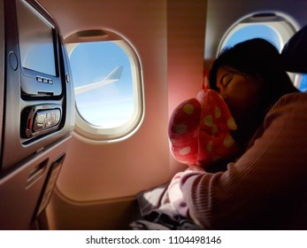 Tired black casual asian lady napping on the seat while traveling by airplane. Commercial transportation by planes.