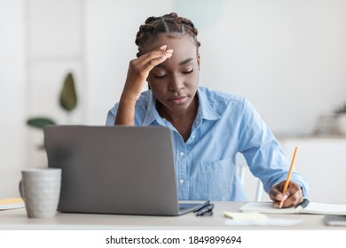 Tired black female office employee sitting at desk with laptop, taking notes, busy young african american secretary focused on work, overworked millennial lady feeling fatigue at workplace, copy space