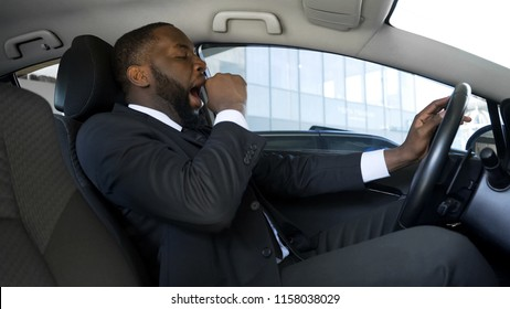 Tired black man yawning in car, overworked businessman driving car, danger