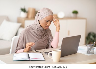 Tired black woman in hijab failing to meet deadline, having difficulty with business project, overworking near laptop at home. Exhausted Muslim female student passing hard online exam