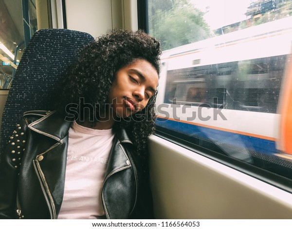 Tired black woman sleeping on the train