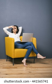 Tired black-haired and  barefoot Armenian girl on yellow chair with laptop and eyes closed.Copy space