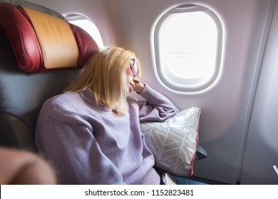 Tired blonde casual caucasian woman sleeping on seat while traveling by airplane on long distance transatlantic flight. Commercial transportation by planes.